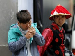 Shop assistance Shao Fei lights a cigarette as his colleague, dressed in traditional costume for promoting their souvenir shop, looks at him at a shopping district in Beijing